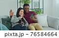 Man and woman making video call, taking selfie sitting on a sofa together at home. Happy multinational couple talking on smartphone making video call at home laughing gesturing enjoying modern 76584664