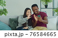 Young mixed race couple sitting on sofa in living room at home making photo, filming video online for blog chatting in net video chat remotely. 76584665