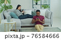 Bored distant young mixed ethnicity couple ignoring each other. Smartphone addicted couple use smartphones sit on sofa at home, overuse social media. Stay at home self-quarantine coronavirus. 76584666