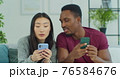 Young mixed ethnicity couple using smartphone while sitting on sofa at home. Couple is spending freetime in social media, using smartphone. 76584676