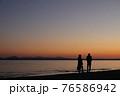 心地よい波の音がする夕暮れの浜辺で語らう恋人 76586942
