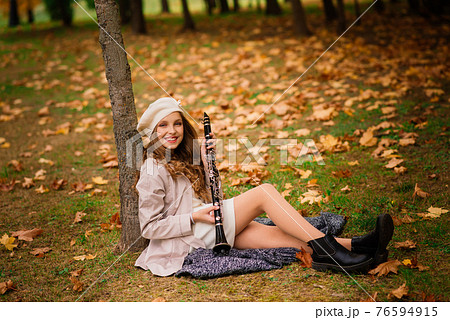 Young attractive girl with clarinet, ebony in fall park 76594915