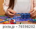 child's hands playing with children's electronic designer. 76598202