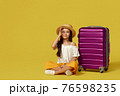 little girl with suitcase and passport sitting on floor 76598235