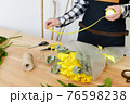 Florist makes a bouquet of fresh yellow tulips. 76598238