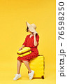 woman with suitcase going traveling on yellow background. 76598250