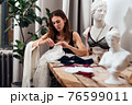 Female lingerie designer works in her workshop with fabric. 76599011