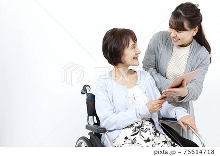 車椅子に乗るシニア女性にタブレットPCを見せる女性 76614718