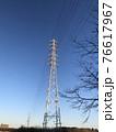冬の青空と高圧鉄塔と高圧線が連なる街並みの風景 76617967