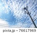 秋の鱗雲と電信柱と電線がある風景 76617969