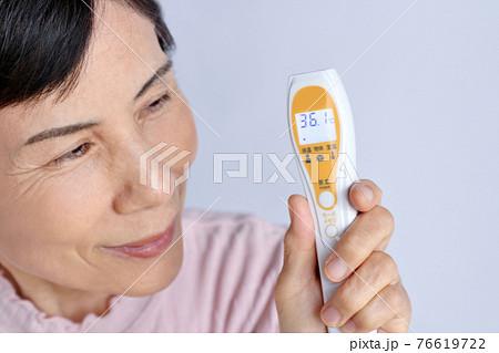 非接触型体温計の体温36.1度に安堵しているシニア女性 76619722