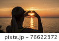 A woman looks at the sea where the sun sets, shows a heart-shaped figure 76622372