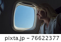 Young woman traveling in an airplane, looking at the sky through the porthole 76622377