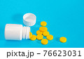Yellow pills and plastic white bottle 76623031