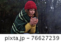 Young woman drinks tea by the fire in the winter forest 76627239