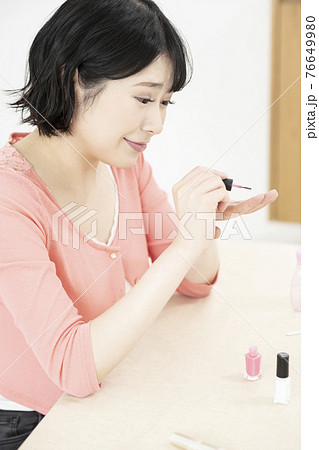 部屋でマニュキュアを塗る若い女性 76649980