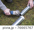 hands of man cutting the stove pipe, working with portable grinder machine on the grass 76665767