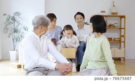 リビングでリラックスする三世代家族 76675687