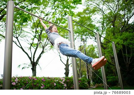 鉄棒で遊ぶ女の子 76689003