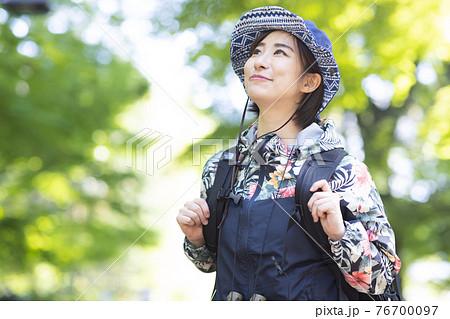 新緑の森でハイキングを楽しむ女性 76700097