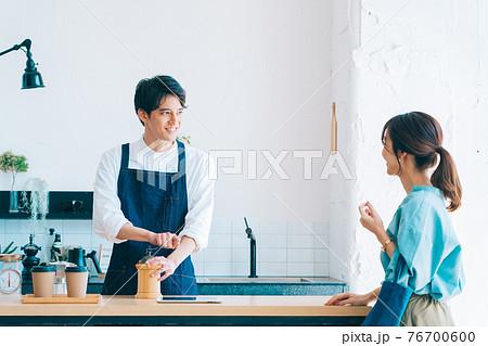 コーヒー豆を挽く男性カフェスタッフと女性客 76700600