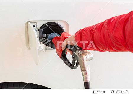 セルフスタンドで給油をする男性 76715470