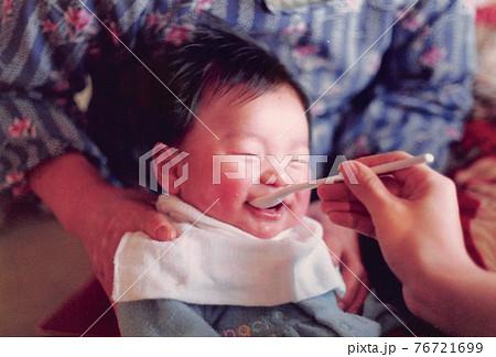 昔のフィルム写真 ごはんを食べて笑っている幼児 76721699