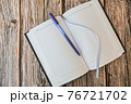 Opened diary or notebook for notes with pen on wooden table top view 76721702