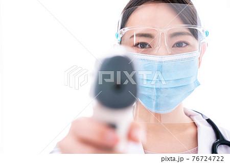非接触体温計で体温測定をする女性医師 76724722