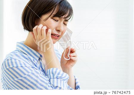 マスクをつけて困る女性 76742475