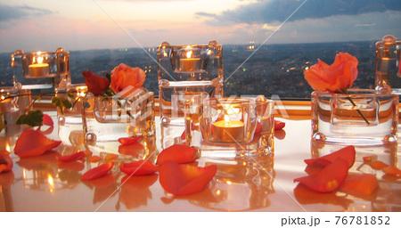 夕日を背にともるキャンドルとバラの花びら 76781852