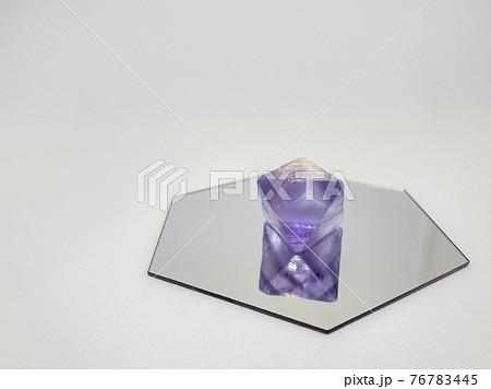 六角形の鏡に置いた八面体の紫色の蛍石 76783445