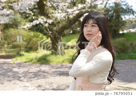 サクラ咲く公園で微笑む若く美しい女性 76795051