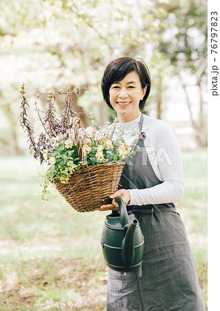 ビオエラの寄せ植えカゴを持つ日本人女性 76797823
