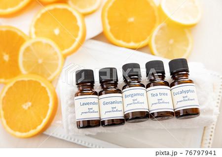 アロマオイルの瓶とフルーツ(オレンジとレモン) 76797941