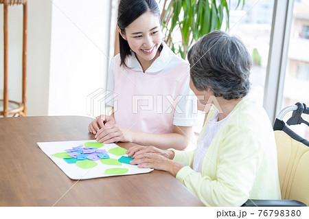 介護イメージ 折り紙をするシニア女性と介護士 76798380