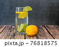 Glass of refreshing lemon and lime fruit drink on wooden table 76818575