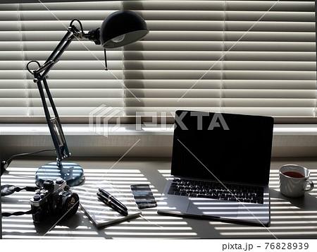 机の上に置かれたフィルムカメラと万年筆 76828939