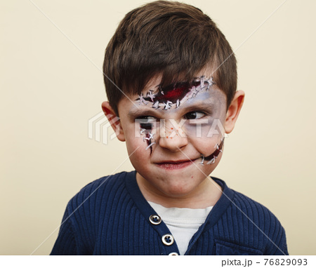 little cute child with facepaint on birthday party, zombie Apocalypse facepainting, halloween preparing concept, lifestyle people 76829093