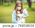 Little girl with dog wearing protective medical mask for prevent virus outdoors in the park 76858638
