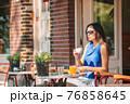 Woman having breakfastin outdoor restaraunt 76858645