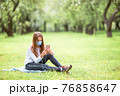 Adorable little girl in blooming apple garden on beautiful spring day 76858647