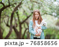 Little smiling girl playing and hugging puppy in the park 76858656