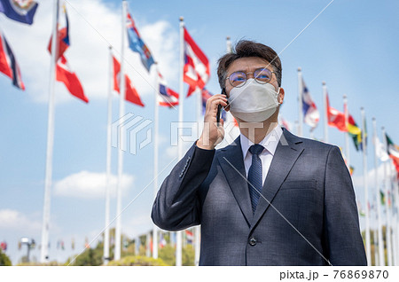 Middle-aged Asian businessman using a smartphone under various national flags fluttering in the wind. 76869870