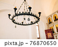 8-light wrought iron black metal chandelier with wax candles in the church. 76870650