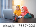 muslim children wearing head scarf smiling while using laptop computer 76874228