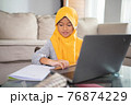 muslim child wearing head scarf smiling while using laptop computer 76874229