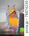 excited young muslim kid while studying online from home 76874230