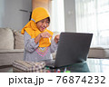 excited young muslim kid while studying online from home 76874232