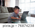 boy using laptop at home 76874238